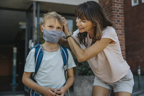 Mother helping son to wear protective face mask while going to school - MFF06359