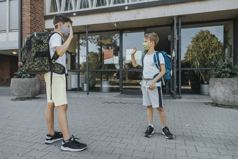 Brothers waving while wearing protective face mask standing in front of school building - MFF06362