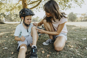 Mother putting bandage on son's knee while sitting in public park during sunny day - MFF06380