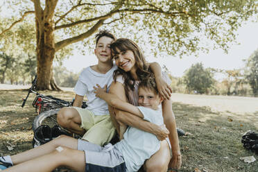 Mother embracing sons while sitting in public park on sunny day - MFF06383