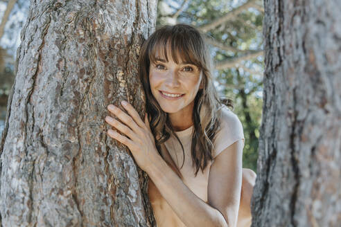 Mature woman leaning on pine tree in public park - MFF06404