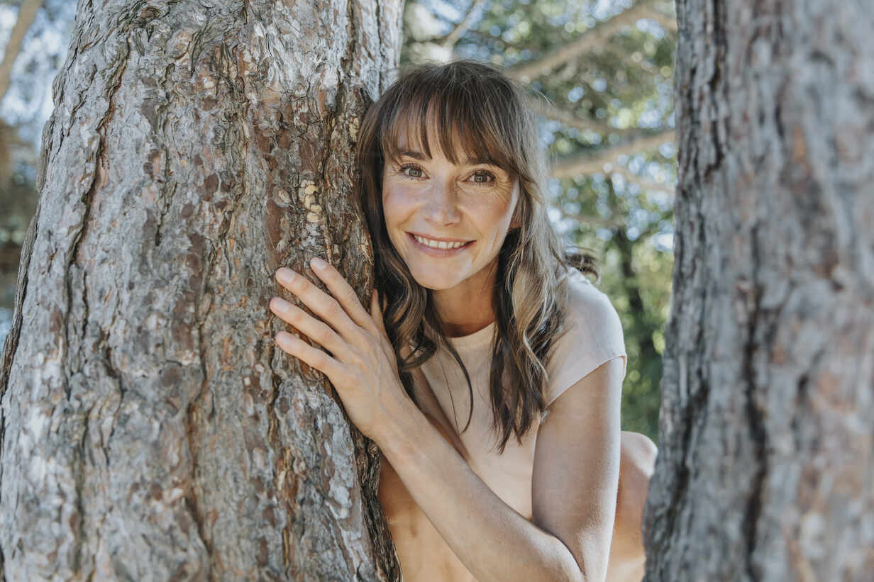 Mature woman leaning on pine tree in public park - MFF06404 - Mareen Fischinger/Westend61