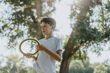 Boy throwing frisbee ring while standing in public park - MFF06407