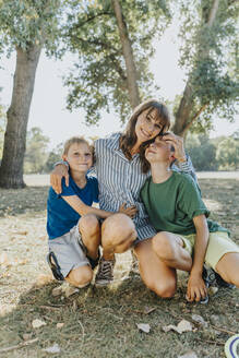 Happy mother embracing sons while kneeling in public park on sunny day - MFF06416