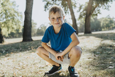 Smiling boy crouching in pubic park on sunny day - MFF06422