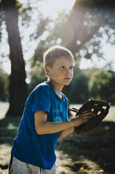 Little boy wearing baseball glove while standing in public park on sunny day - MFF06425