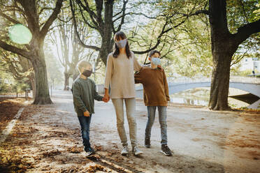 Mother and sons wearing protective face mask while walking in public park during covid-19 - MFF06434