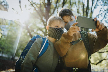 Brothers taking selfie on smart phone wearing protective face mask standing in public park - MFF06440