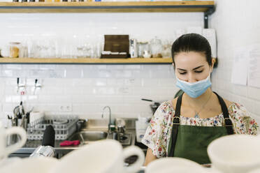 Woman wearing face mask while working in kitchen at coffee shop - XLGF00596