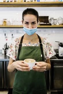 Young woman wearing face mask and apron with coffee cup standing at coffee shop - XLGF00599