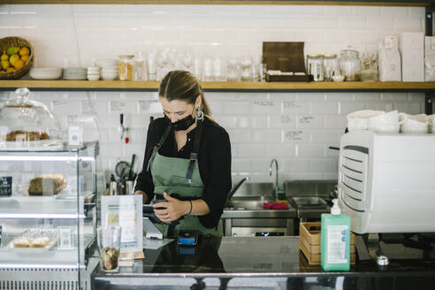 Businesswoman with face mask using digital tablet while standing at coffee shop - XLGF00614