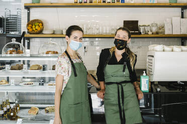 Partners wearing face mask and apron standing by counter at coffee shop - XLGF00617
