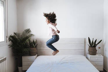 Cute girl jumping on bed in bedroom at home - EBBF00934