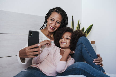 Mother and daughter taking selfie on smart phone sitting in bedroom at home - EBBF00940