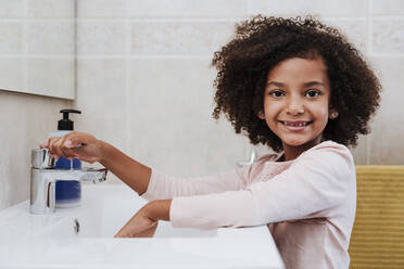 Smiling girl washing hands at home - EBBF00949