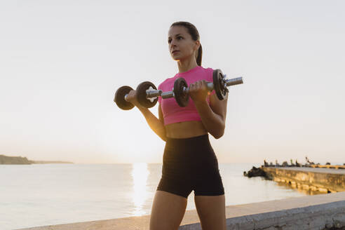Sportswoman picking dumbbell while standing against sea - AFVF07373