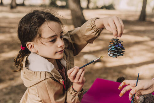 Cute girl holding pine cone while coloring by sister at park - ERRF04612