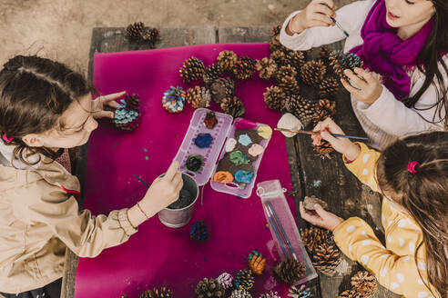 Sisters decorating pine cones while coloring at picnic table in park - ERRF04624