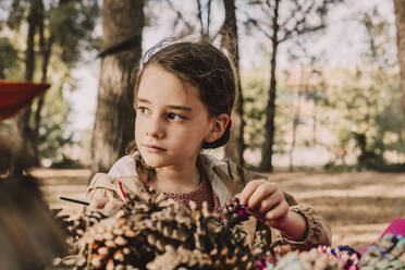 Cute girl looking away while coloring pine cone at park - ERRF04627