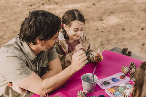 Smiling girl coloring pine cone with father while sitting at picnic table in park - ERRF04636
