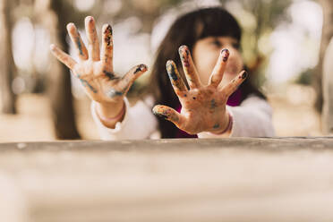 Girl with messy hands at picnic table in park - ERRF04639