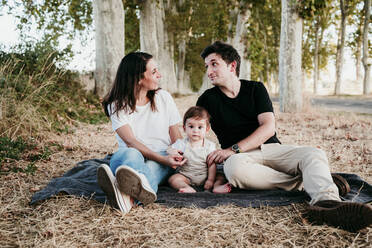 Couple talking while sitting with baby boy on blanket outdoors - EBBF00991