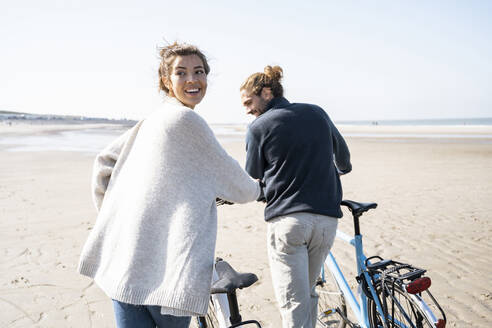 Smiling young woman walking with bicycle and boyfriend while looking over shoulder at beach against clear sky on sunny day - UUF21762