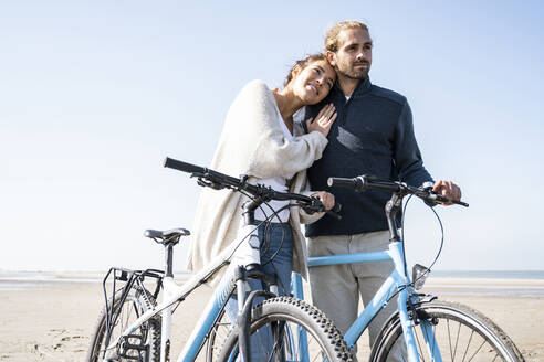 Smiling beautiful woman with head on boyfriend's shoulder standing with bicycles at beach against clear sky on sunny day - UUF21765