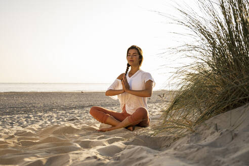 Young woman practicing yoga while sitting by plant on sand at beach against clear sky during sunset - UUF21771