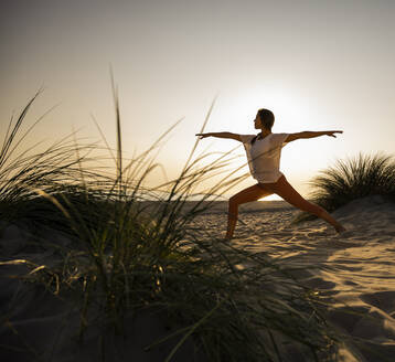 Young woman practicing warrior 2 position yoga at beach against clear sky during sunset - UUF21780