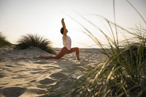 Flexible woman practicing yoga on sand at beach during sunset - UUF21783