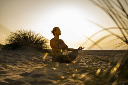 Shirtless man meditating while practicing yoga on sand at beach against clear sky during sunset - UUF21786