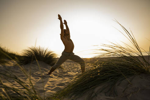 Shirtless young man practicing warrior position yoga amidst plants at beach against clear sky during sunset - UUF21789