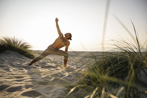 Shirtless young man practicing triangle position yoga at beach against clear sky during sunset - UUF21792