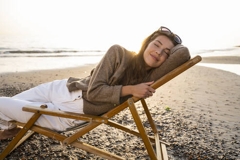 Smiling beautiful young woman reclining on folding chair while relaxing at beach during sunset - UUF21801