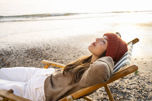 Young woman relaxing on folding chair with eyes closed at beach during sunset - UUF21810