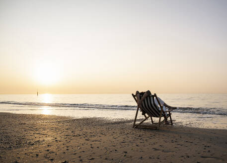 Woman relaxing while sitting on folding chair at beach against clear sky during sunset - UUF21819