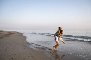 Cheerful man giving piggyback to girlfriend on shore at beach against clear sky during sunset - UUF21828