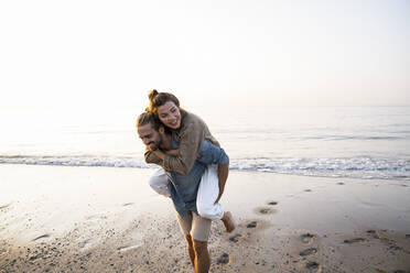 Happy man giving piggyback to girlfriend while walking on shore at beach against clear sky during sunset - UUF21831