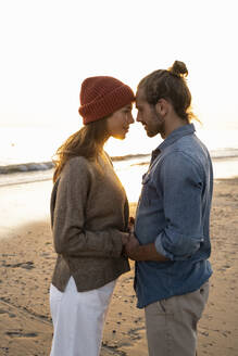 Young romantic couple looking at each other while standing on shore during sunset - UUF21834