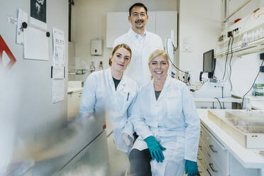 Coworkers smiling while sitting with scientist standing in background at laboratory - MFF06485