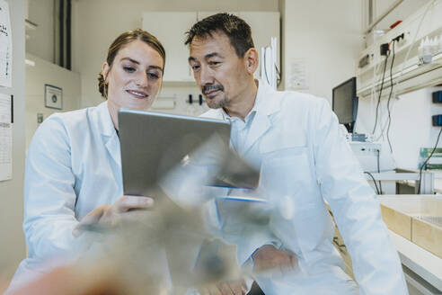 Assistant and scientist using digital tablet while sitting at laboratory - MFF06488