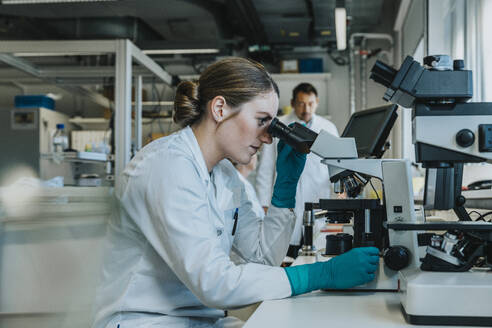 Young woman analyzing human brain microscope slide under microscope while sitting with scientists in background at laboratory - MFF06494