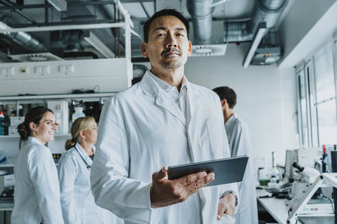Scientist with hand in pocket and digital tablet standing with coworkers in background at laboratory - MFF06557
