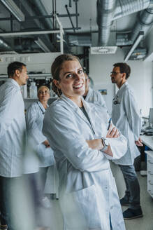 Young scientist smiling while standing with arms crossed and coworker in background at laboratory - MFF06563