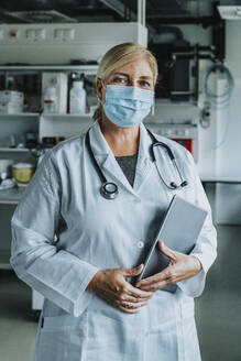 Scientist with face mask and digital tablet standing at laboratory - MFF06578