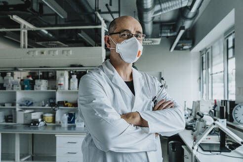 Confident scientist wearing face mask standing with arms crossed at laboratory - MFF06584