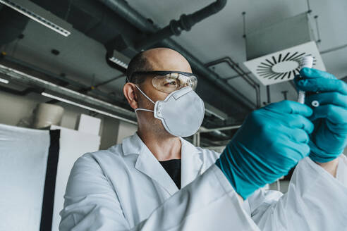 Scientist wearing protective face mask and eyeglasses holding vaccine while standing at laboratory - MFF06587