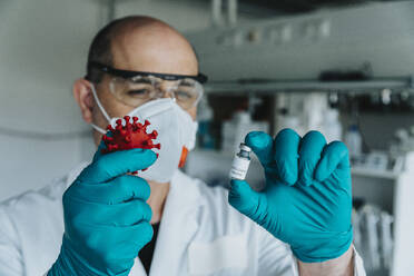 Scientist with face mask holding vaccine and coronavirus model while standing at laboratory - MFF06590