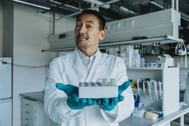 Confident scientist showing test tube tray while standing at laboratory - MFF06596